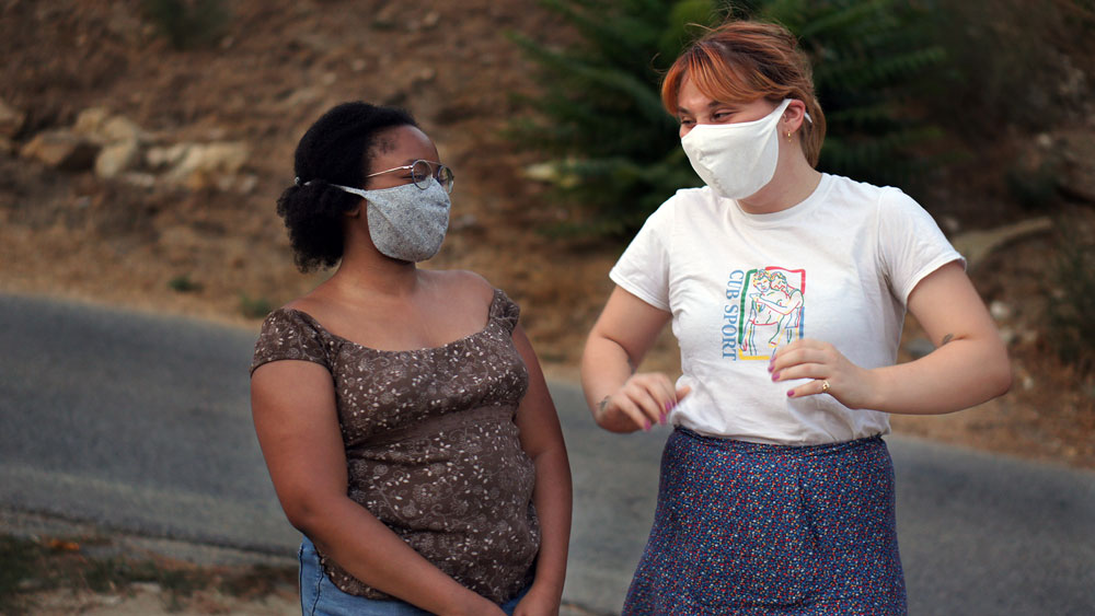 Women wearing coronavirus face masks and talking | Out and About Supply