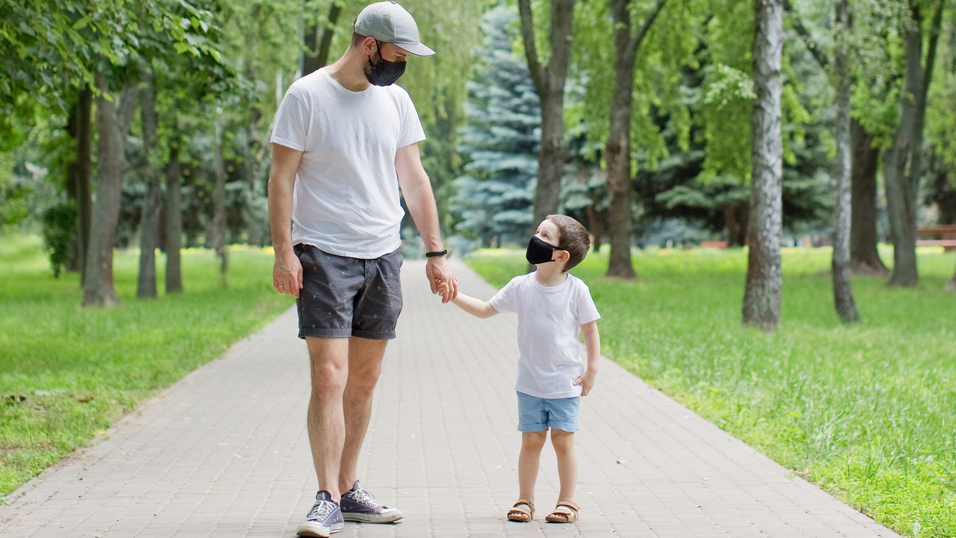 Man and kid wearing black antiviral face masks | Out and About Supply